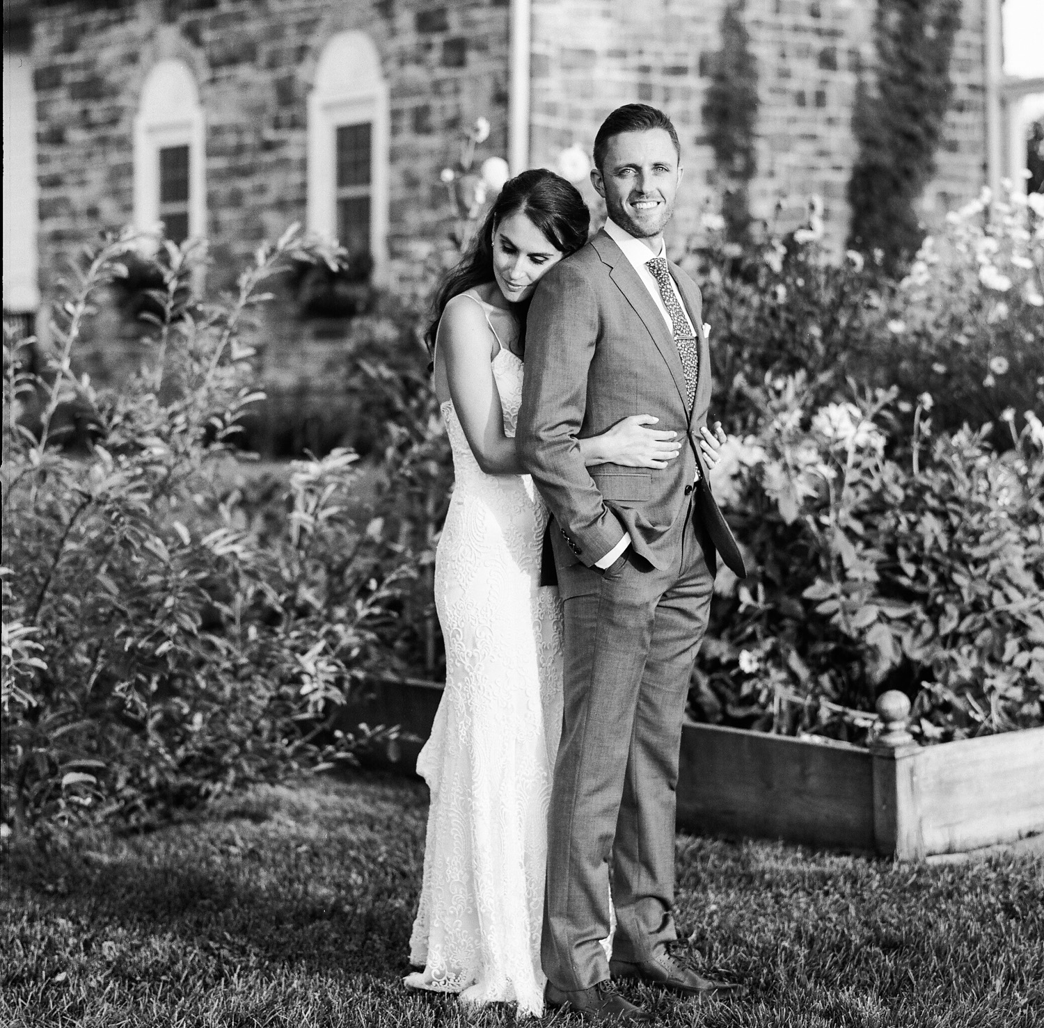 image of bride in modern troussea gown and groom portrait in garden at private estate Gettysburg