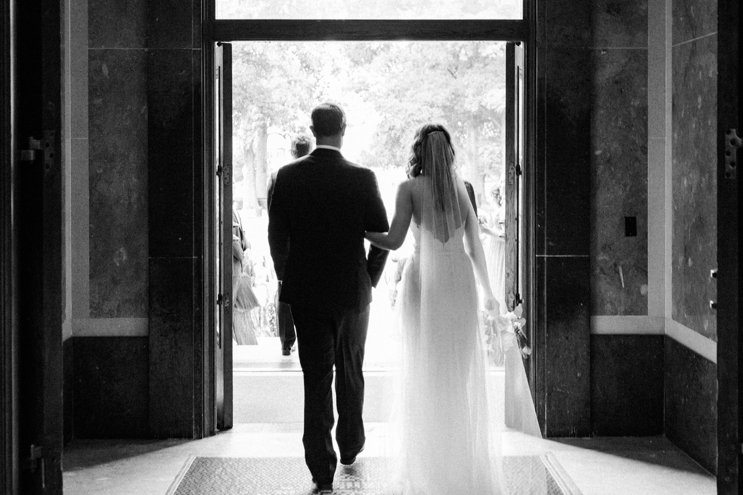 image of bride and groom exit US Naval Academy chapel wedding ceremony in black and white