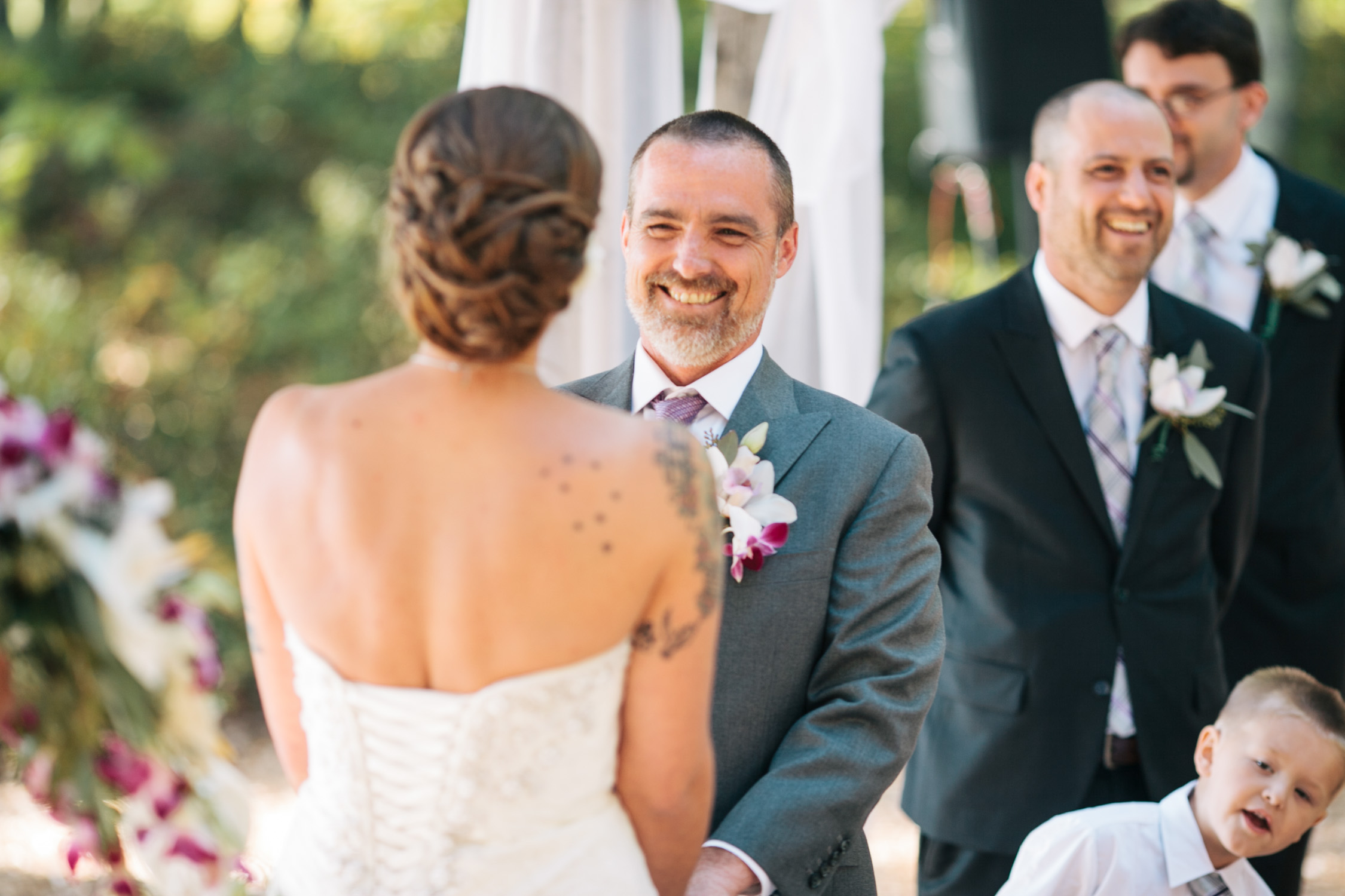 image of groom smiling at tattoo bride at wedding ceremony