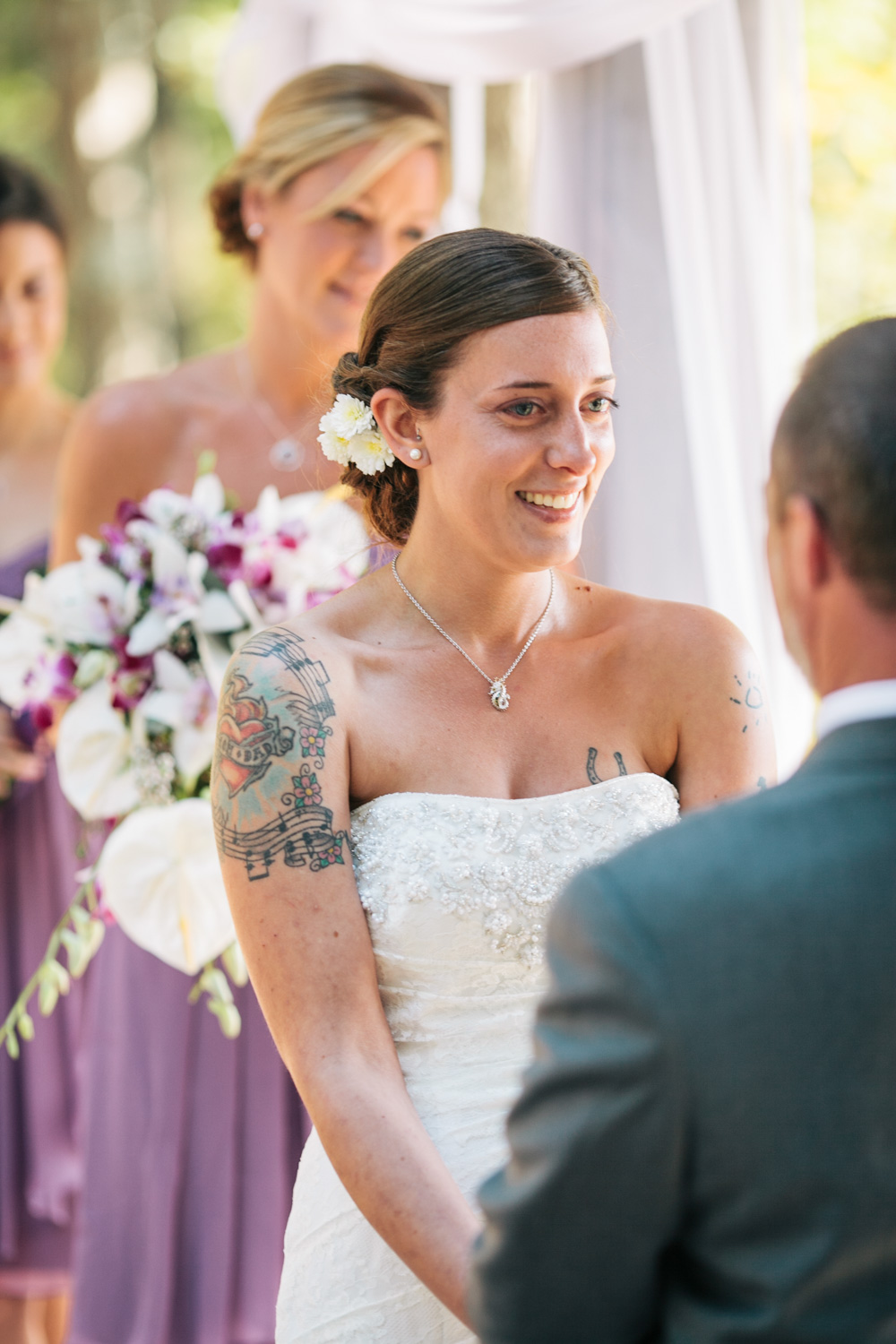 image of tattoo bride smiling at groom during wedding ceremony