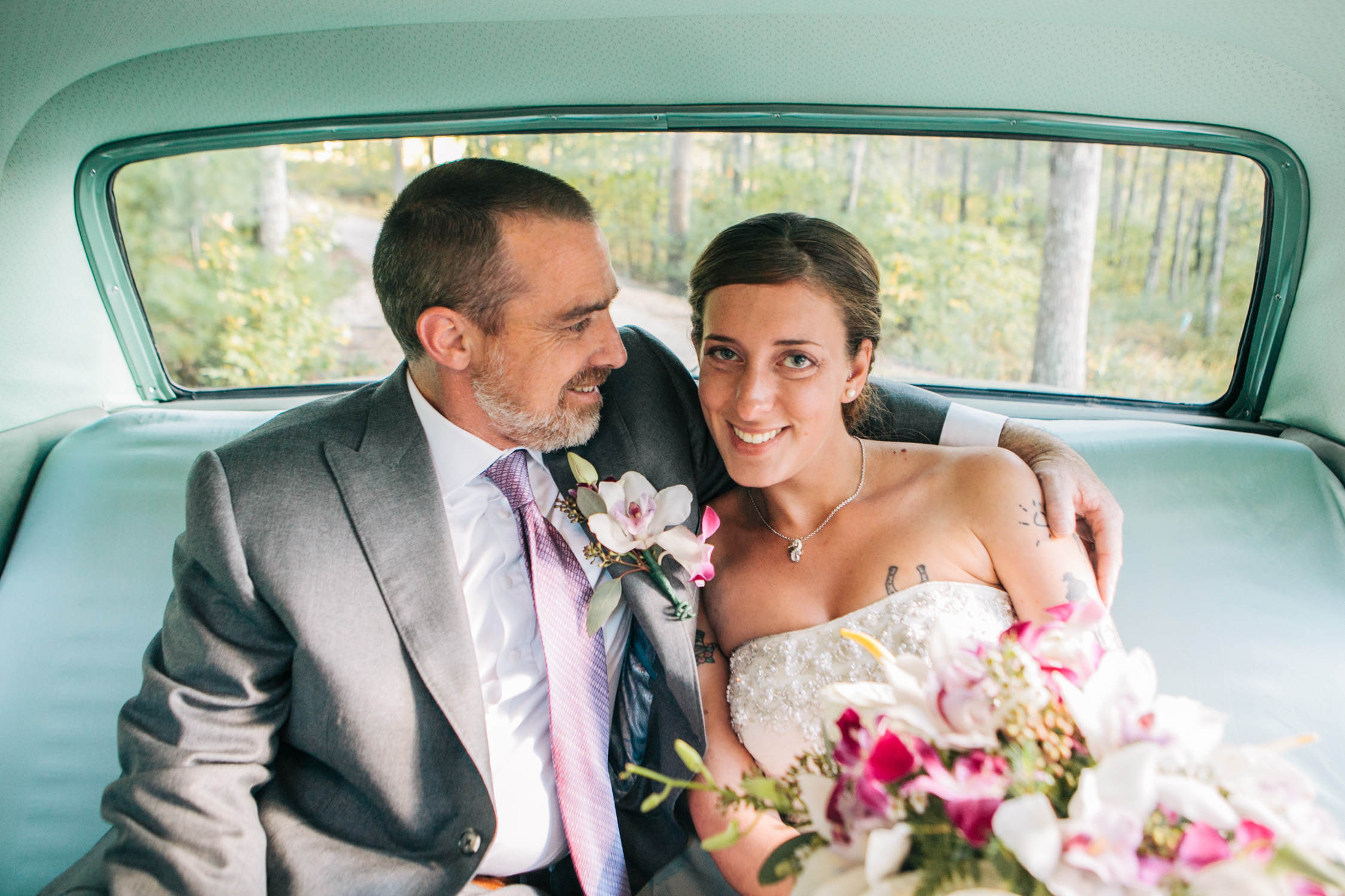 image of bride and groom exit ceremony in backseat of classic car