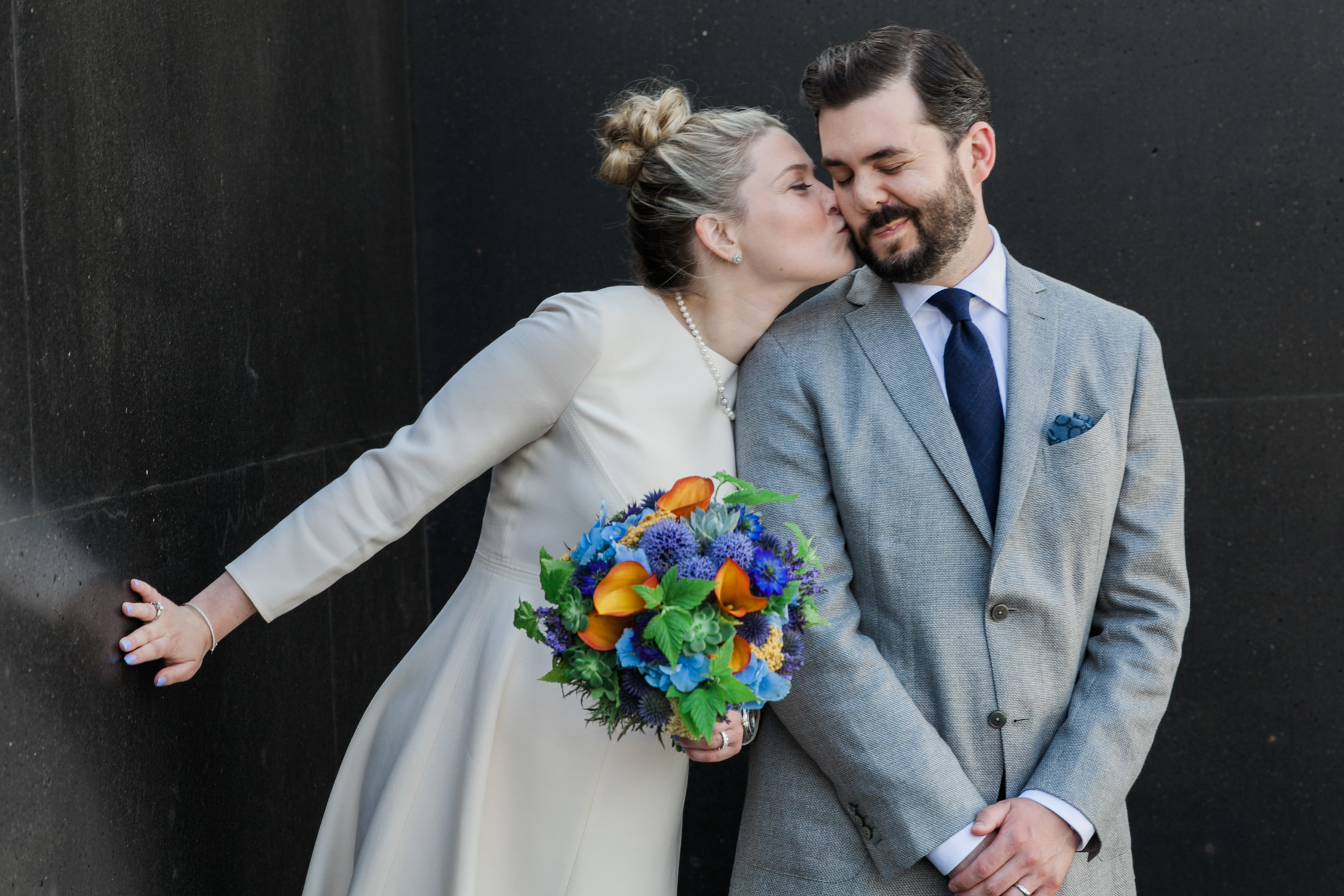 image of bride and groom colorful bouquet cute kiss at Canlis restaurant