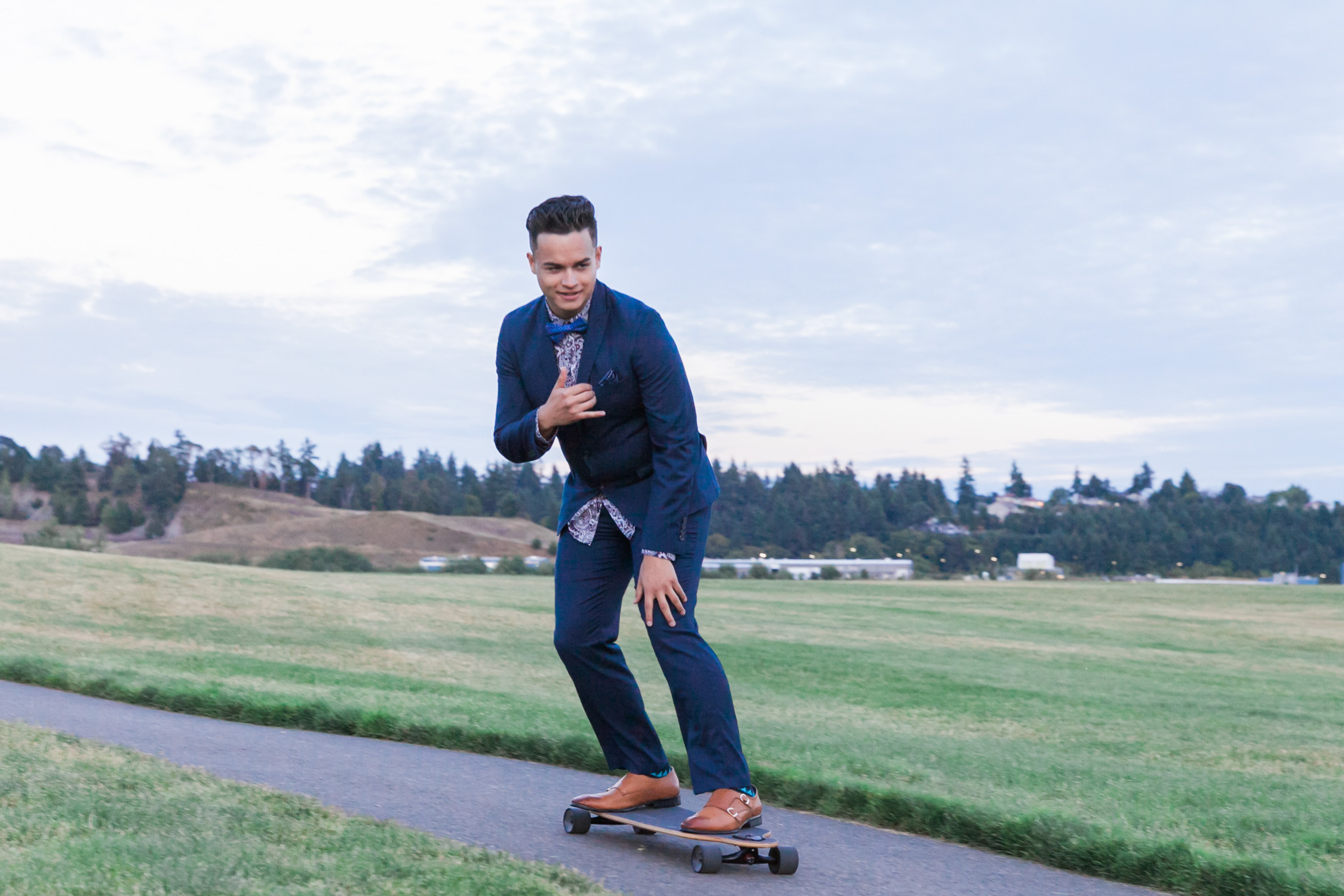 image of senior portrait boy in suit skateboarding at Chambers Bay in University Place